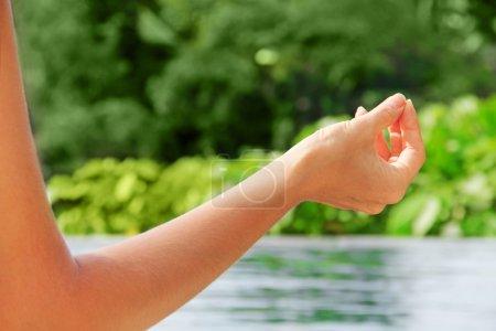 Woman meditating on the swimming pool