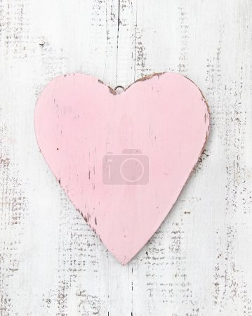 Retro pink wooden heart on a white background