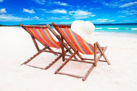 Two wooden sun loungers on white sand