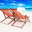Two wooden sun loungers on white sand...