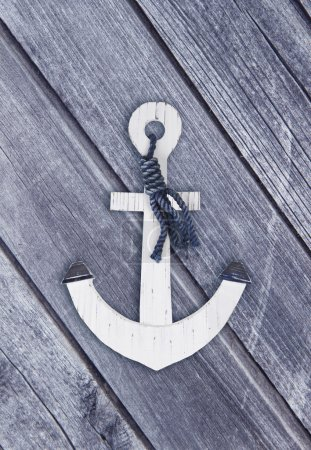 White wooden anchor on the background of wooden boards