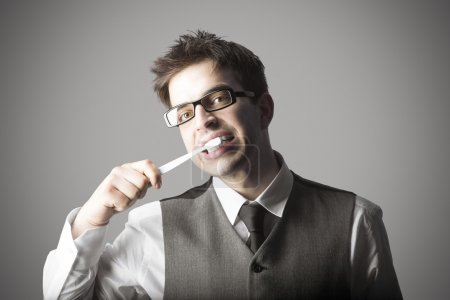 Young stylish man with eyeglasses brushing teeth