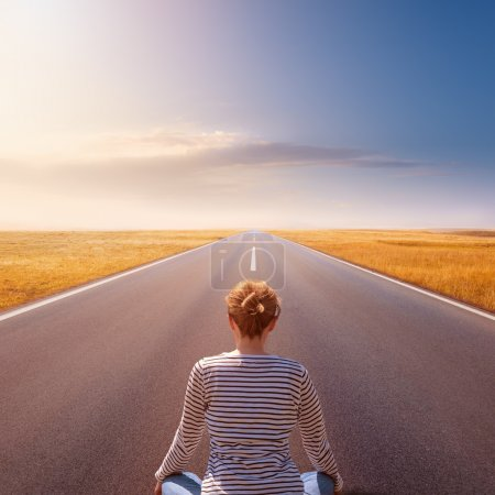 Photo for Lonely girl meditating on the open road - Royalty Free Image