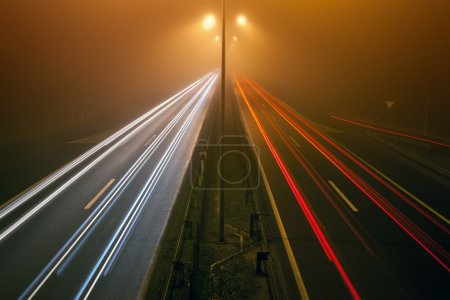 Night traffic on a highway in the fogy night