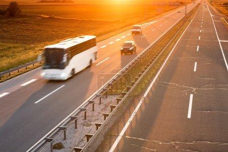 Photo pour Bus blanc en motion blur sur autoroute au coucher du soleil - image libre de droit