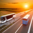 Two buses on highway in motion blur at sunset...