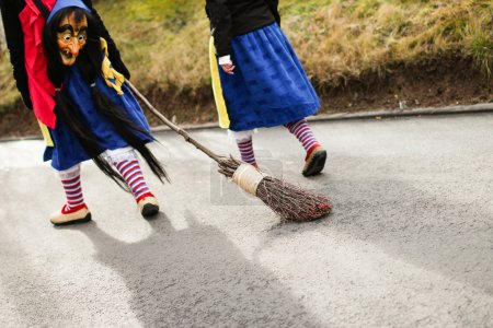 Traditional carnival in South Germany - Swabian-Alemannic Fastnacht. Two witches walking down the street. Selective focus on broom.