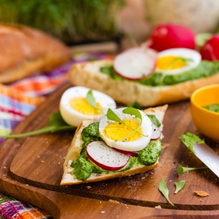 Photo for Baguette with green pesto, radish slices and eggs, Selective focus - Royalty Free Image