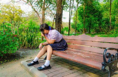 High-Schoolgirl hiding from something on the bench