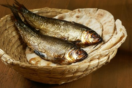 Photo for Loaves of bread and two fishes in a basket. - Royalty Free Image