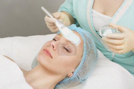 Girl gets a facial mask beautician