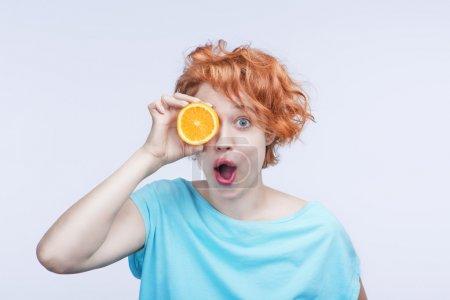 Photo pour Fille jeune rousse avec des yeux brillants de gros en chemise bleue tient demi-orange le lieu oeil. fond gris. Studio tourné - image libre de droit