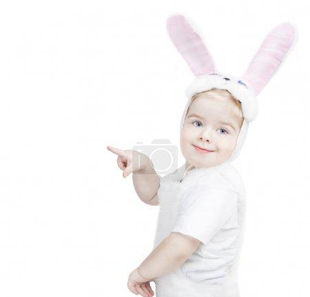 Cute little boy in a rabbit costume shows a finger...