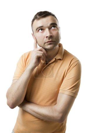 Photo pour Jeune homme regardant vers le côté avec attention. Examine tes informations. Fond blanc studio tourné . - image libre de droit