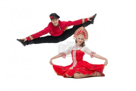Photo for Couple of dancers in russian traditional costumes, girl in red sarafan and kokoshnik, boy in black trousers and red shirt   Man makes a jump  Studio shot isolated on white - Royalty Free Image