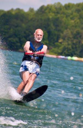 Photo pour Un senior actif démontre sa forme physique sur un ski de slalom . - image libre de droit