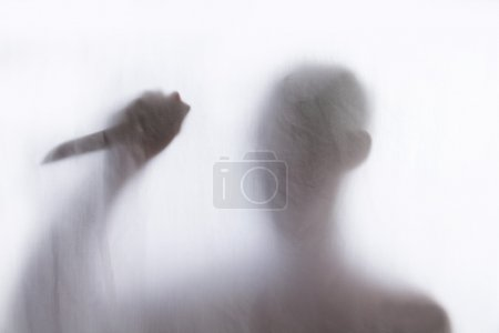 Shadow of men standing behind thin fabric and holding a knife