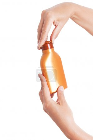 Hands holding plastic bottle for sun lotion isolated on white ba