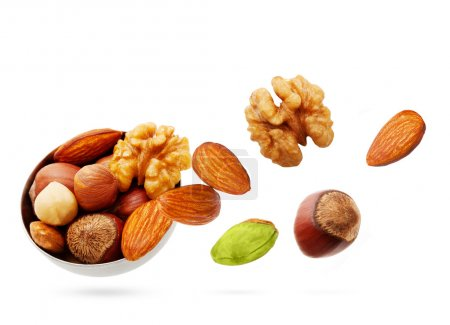 Photo for Falling nuts in bowl isolated on white background. - Royalty Free Image
