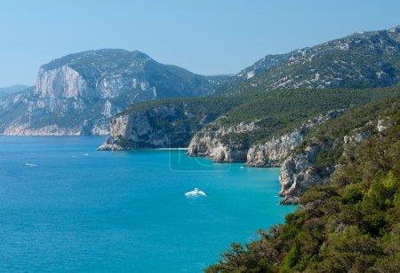 Photo pour Vue sur la plage populaire de Cala Luna Sardaigne, Italie, destination populaire en Sardaigne, mer cristalline avec les petits bateaux et le fond de montagnes brumeuses à Cala Luna, paysage sardinien, nature sardinienne, mer émeraude, plage populaire en Sardaigne - image libre de droit