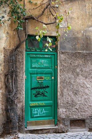 A weathered green door of Rome, Italy, Europe. Old wooden door with various writings in Italy, a green wood old door in the centre of Rome, Italy. Old door.