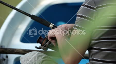 Close up shot of young man fishing on the boat