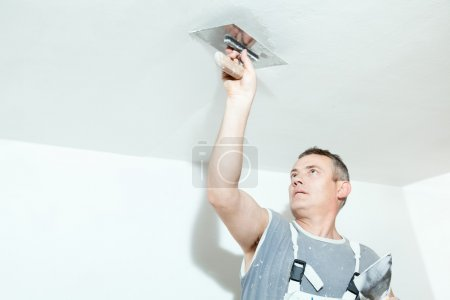 Photo for Plasterer spreading out plaster with trowel over the ceiling - Royalty Free Image