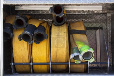 Rolled and yellow fire hoses on a fire truck
