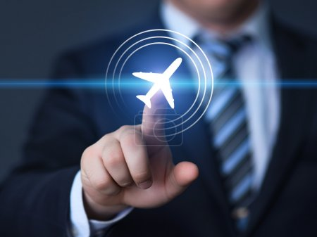 Businessman pointing finger to select a flight by pressing a touch screen airplane button