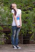 Asijská dívka stojící mezi listy