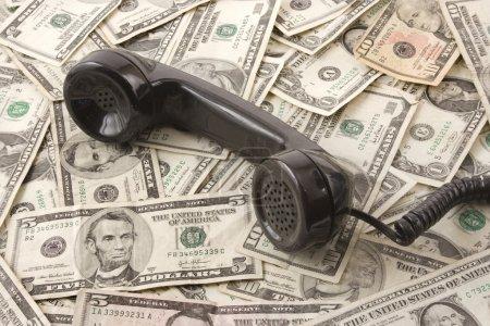 Foto de Negro teléfono sobre fondo de nosotros dinero. - Imagen libre de derechos