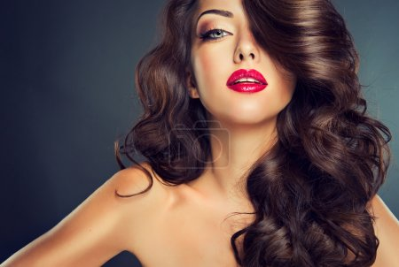 Photo for Beautiful sensual brunette woman with long curly hair on blue background - Royalty Free Image