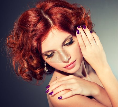 Woman with bright makeup and manicure looking down