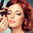 Artist doing glamour model makeup to red-haired gi...