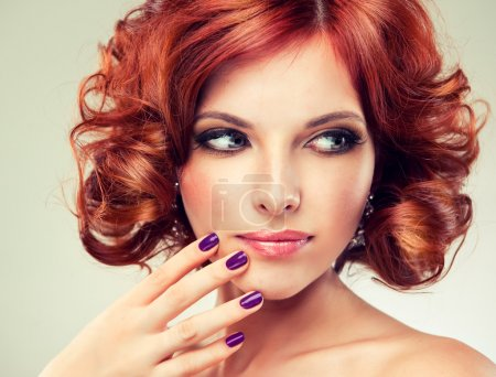 Photo for Beautiful young redhead woman with bright makeup and manicure looking to the left - Royalty Free Image