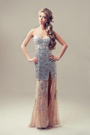 Photo pour Jeune fille vêtue d'une robe magnifique posant sur fond gris - image libre de droit