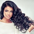 Beautiful brunette woman with long curly hair on g...