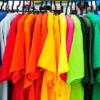 Colorful t-shirt with hangers in market...