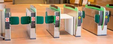 Turnstiles in underground railway station. Green arrows pointing