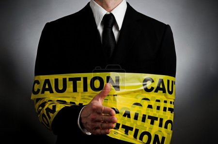 Photo for Image of a man wanting to shake hands wrapped in caution tape - Royalty Free Image