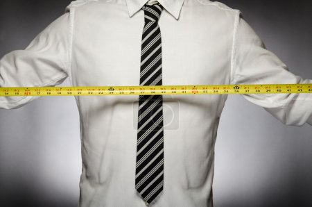 Photo for Man wearing tie with measuring tape - Royalty Free Image