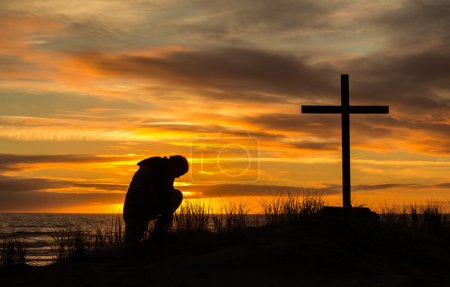 Photo for Beautiful sunset as man bows down to pray God before a cross. - Royalty Free Image