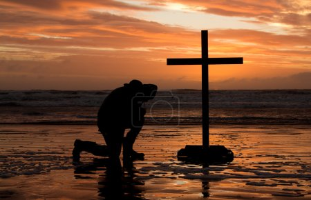 Photo for Man bowing down before a cross at sunset. - Royalty Free Image