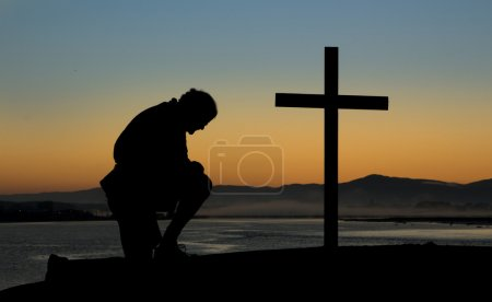 Photo for A man kneeling in prayer by a cross on a hill at dawn of a new day. - Royalty Free Image