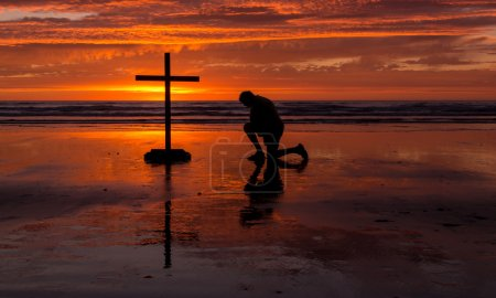 Photo for Praying man by a cross as the sun goes down. - Royalty Free Image