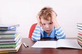 Unavený chlapec sedí u stolu a drželi se za ruce na hlavu