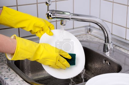 Photo for Womans hands in the gloves wash plate horizontal closeup - Royalty Free Image