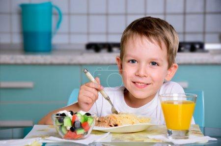 Photo pour Joyeux garçon souriant assis à la table du dîner et regardant la caméra. horizontal - image libre de droit