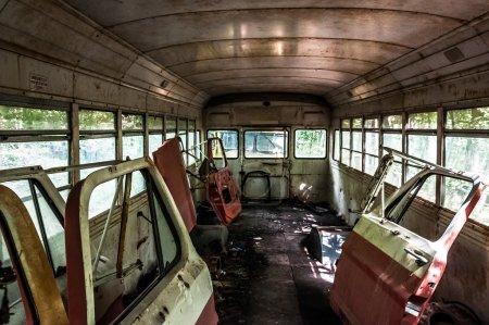 Car doors inside of a old school bus in a junkyard