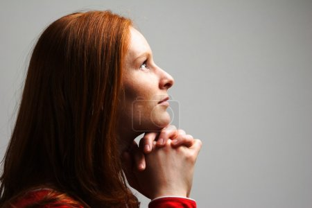 Photo for A young woman praying to God in dramatic lighting and on plain background. - Royalty Free Image